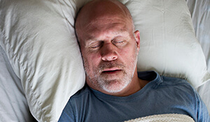 Older man sleeping soundly in bed