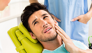 Man in pain holding cheek in dental chair